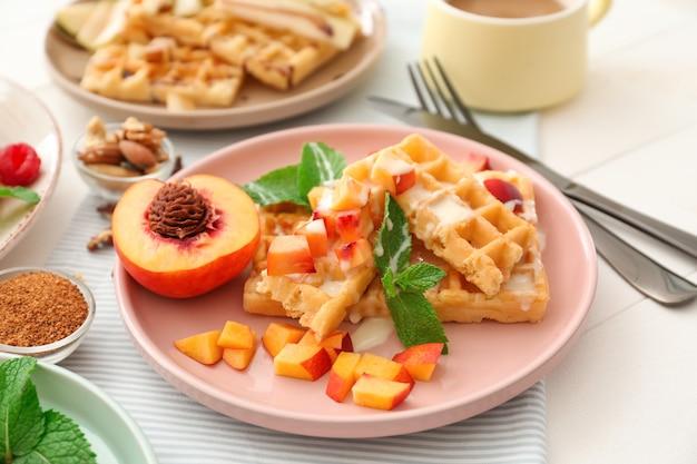 Тарелка с вкусными вафлями и дольками персика на столе