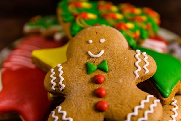 素朴な木製のテーブルにさまざまなクリスマスのジンジャーブレッドクッキーでプレート
