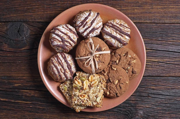 Plate with different cookies on dark wooden table, top view