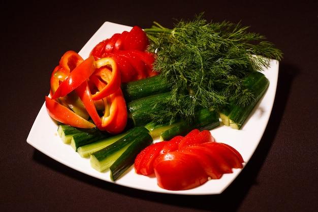 さまざまな新鮮な野菜のトマト、きゅうり、コショウ、緑を盛り付けます。健康的な有機食品の概念