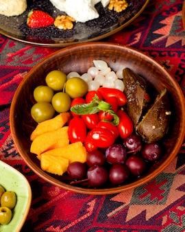 Тарелка с разными солеными огурцами, баклажанами, томатами черри и луком