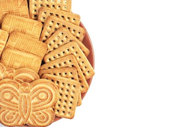 흰색 배경, 위쪽 보기에 격리된 다른 달콤한 쿠키가 있는 접시. 텍스트를 위한 공간
