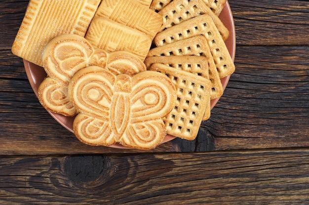 나무 배경에 다른 달콤한 쿠키가 있는 접시, 위쪽 전망. 텍스트를 위한 공간