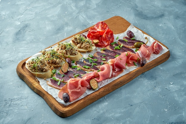 Plate with different types of meat antipasto - sliced prosciutto, chorizo, jerky duck and bruschetta with stew on a wooden board