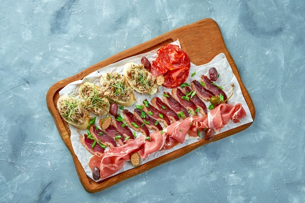 Plate with different types of meat antipasto - sliced prosciutto, chorizo, jerky duck and bruschetta with stew on a wooden board.