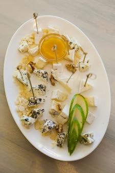 Тарелка с разными видами сыра, меда, грецкого ореха и груши