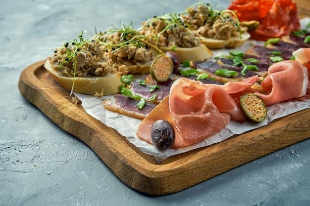 さまざまな種類の肉前菜-スライスした生ハム、チョリソ、ぎくしゃくしたアヒル、ブルスケッタのシチューと木の板。