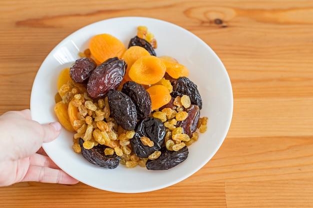 木製のテーブルにドライフルーツを盛り付けます。便利な食べ物-ナツメヤシ、ドライアプリコット、プルーン、レーズン