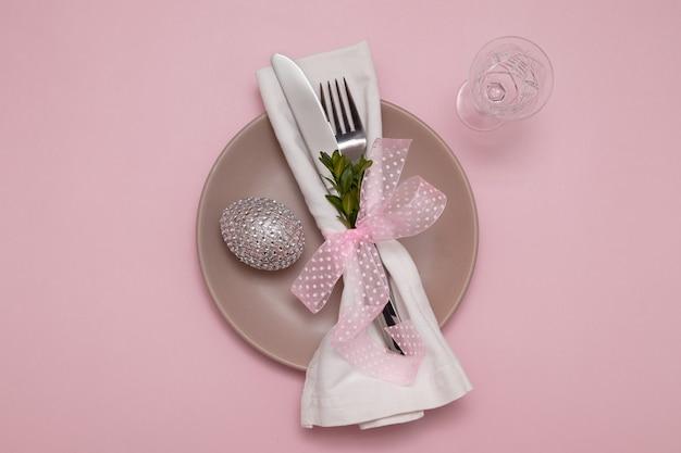 Тарелка с посудой на салфетке и яйцом на пастельно-розовом столе концепция пасхального меню