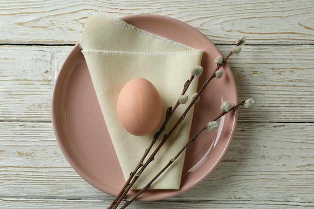 Plate with egg, kitchen napkin and catkins on wooden background