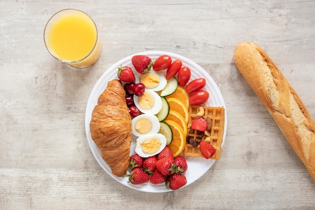 Тарелка с яйцами фрукты и овощи с багетом