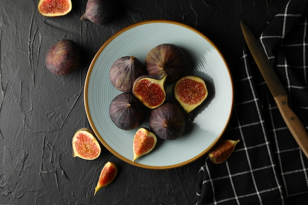 Plate with fig, knife and towel on black, top view