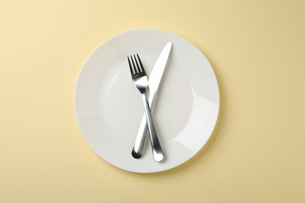 Plate with fork and knife on beige background, top view
