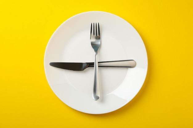 Plate with fork and knife on yellow background, top view