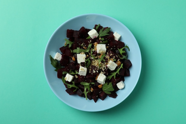Plate with fresh beet salad on mint table