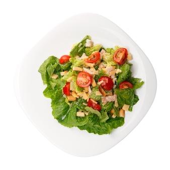 Тарелка со свежим салатом цезарь с курицей, изолированной на белом