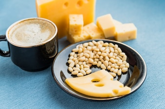Plate with fresh cheese and nuts near cup of drink on table