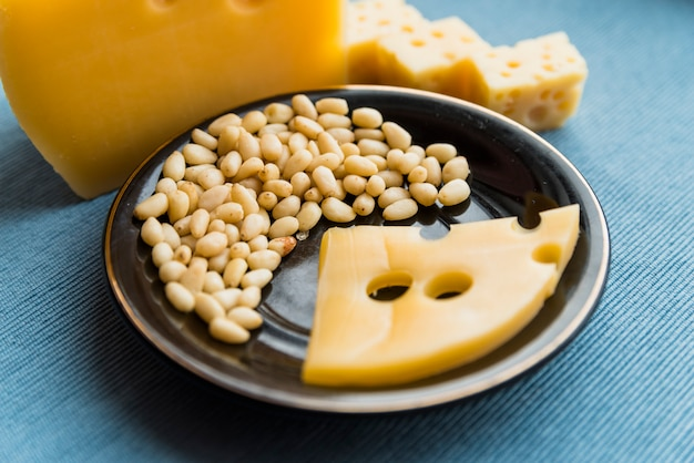 Plate with fresh cheese and nuts on table