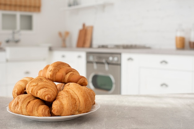 Plate with fresh croissants on table Premium Photo