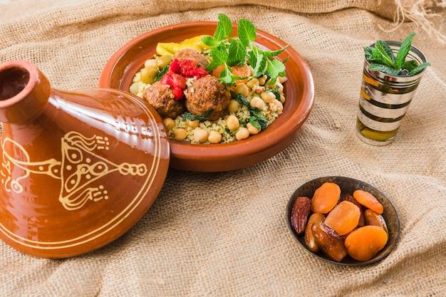 Тарелка со свежими продуктами возле чашки и сушеные фрукты на мешковине