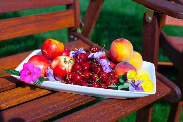 Plate with fresh fruits and flowers on wooden chairs in the garden
