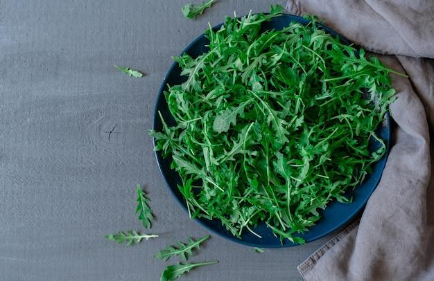 Тарелка со свежей зеленой рукколой на сером фоне Premium Фотографии