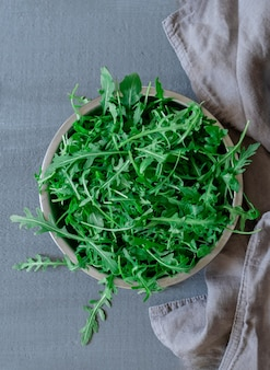 Тарелка со свежей зеленой рукколой на сером фоне