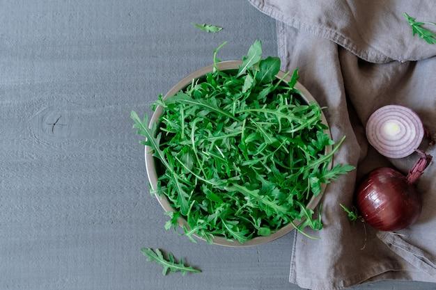 Тарелка со свежей зеленой рукколой, луком и помидорами на сером фоне, вид сверху.