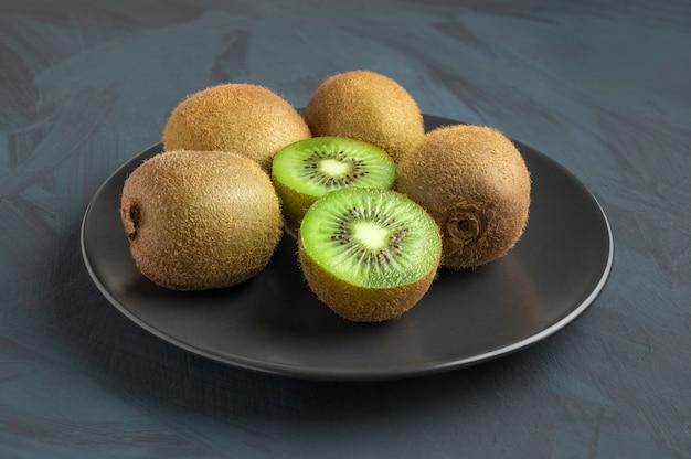 素朴なテーブルに新鮮な緑のキウイのプレート-季節のフルーツ