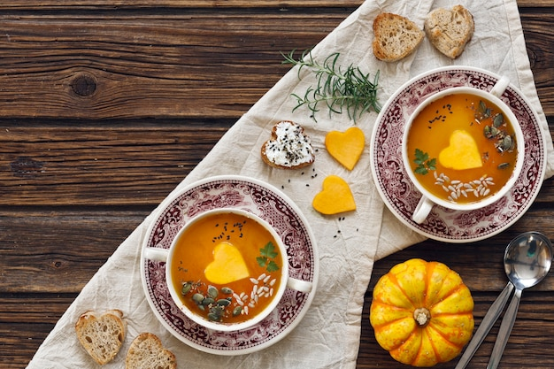 Plate with fresh homemade pumpkin cream soup with seeds and heart shape toasts
