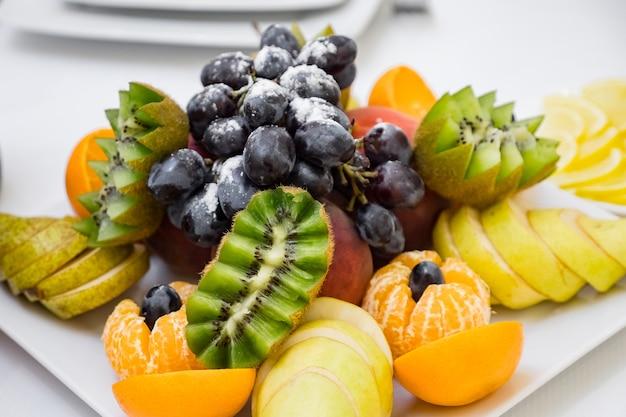 Тарелка со свежими фруктами на столе в кафе