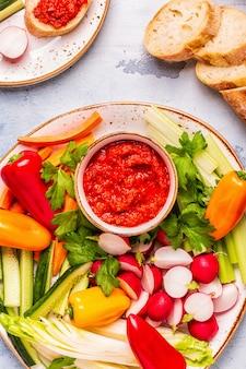Тарелка со свежими сырыми овощами и соусом