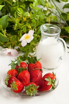 Plate with fresh strawberries with milk