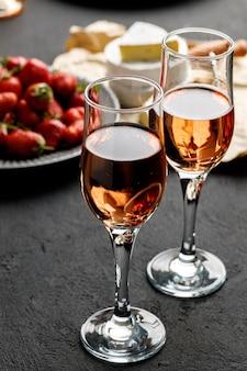 黒の背景に新鮮なイチゴとグラスワインのプレートをクローズアップ
