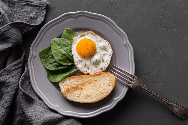 Тарелка с жареным яйцом и хлебом