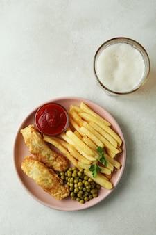 Тарелка с жареной рыбой и жареным картофелем и пивом изолированы
