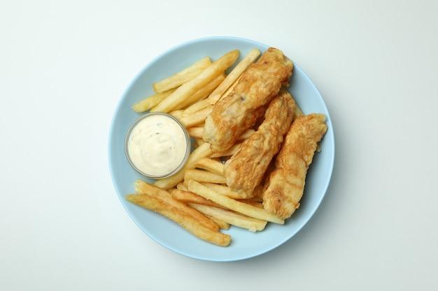 Тарелка с жареной рыбой и жареным картофелем и соусом на белом