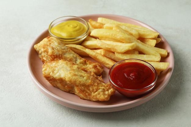 Тарелка с жареной рыбой и жареным картофелем и соусами на белом текстурированном фоне