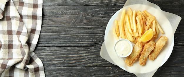 Тарелка с жареной рыбой и жареной картошкой на деревянном с кухонным полотенцем