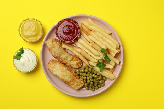 Тарелка с жареной рыбой и жареным картофелем, горохом и соусами на желтом