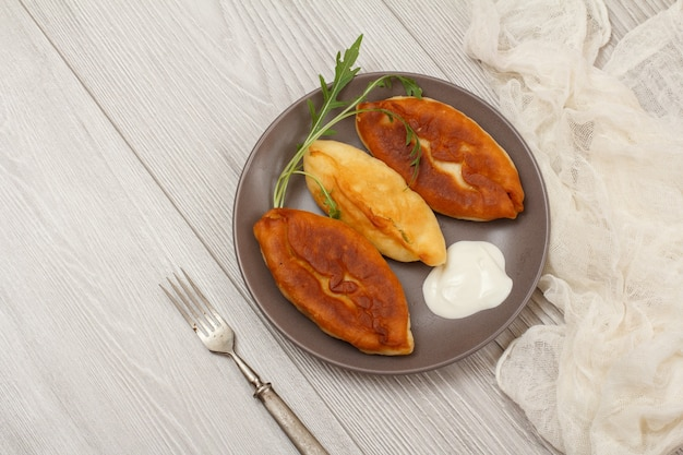 Тарелка с жареными пирогами, сметаной и вилкой, белой марлей на деревянных досках. вид сверху.