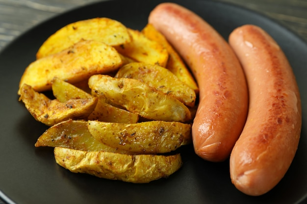 Plate with fried potato and sausage, close up