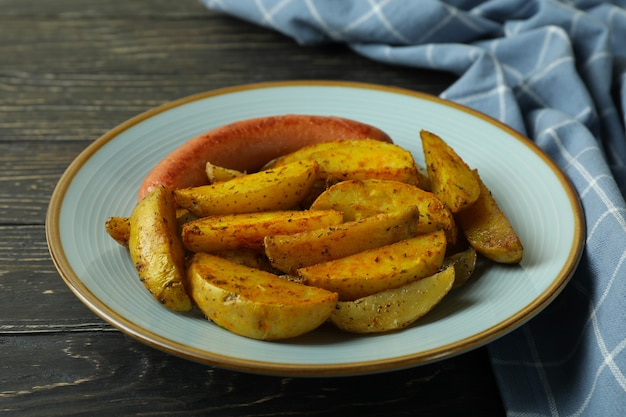Plate with fried potato and sausage, and kitchen towel on wooden background