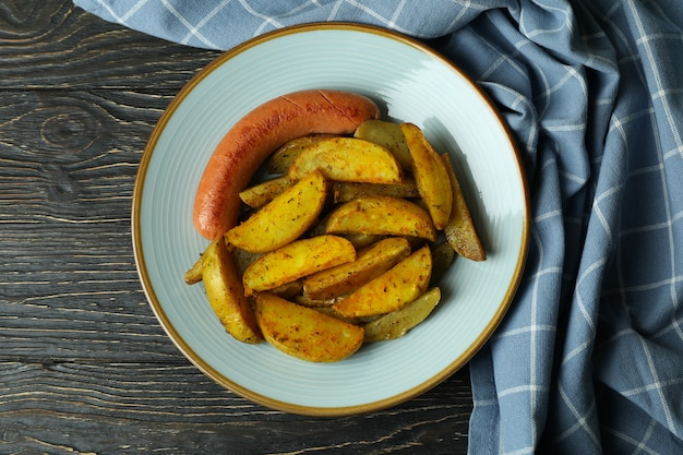Plate with fried potato and sausage, and kitchen towel on wooden