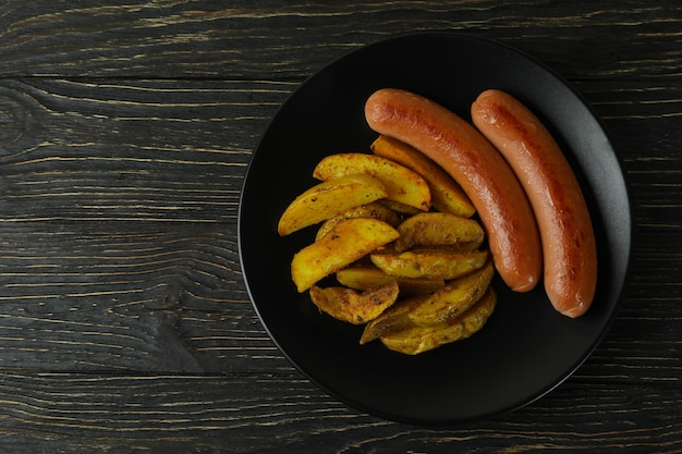 Plate with fried potato and sausage on wooden background