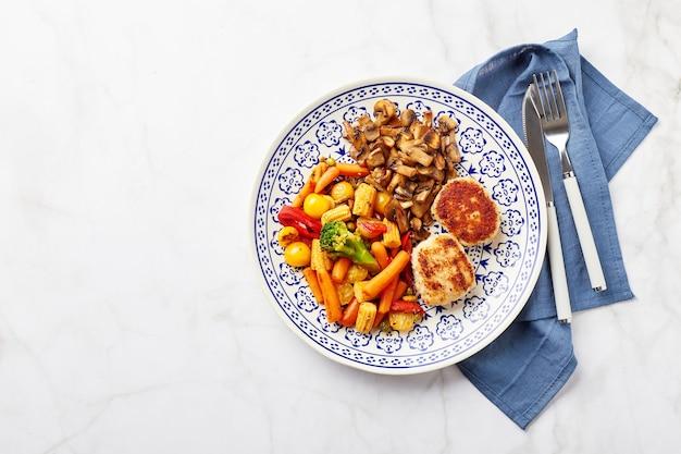 튀긴 야채 당근 브로콜리 베이비 콘 피망 볶은 샴 피뇽과 치킨 볼 2 개가 담긴 접시