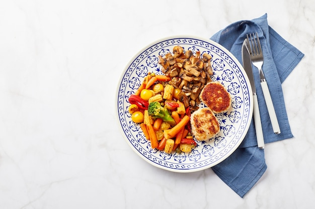 Plate with fried vegetables carrots broccoli baby corn bell peppers roasted champignons and two chicken balls