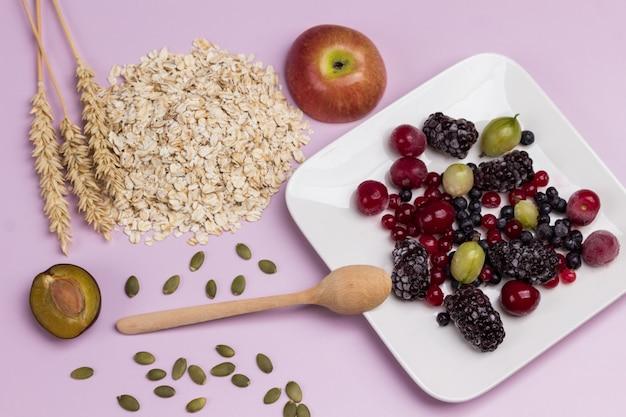 冷凍ベリーを盛り付けます。テーブルの上の小麦とオーツ麦のフレークの小穂。フラットレイ。ピンクの背景