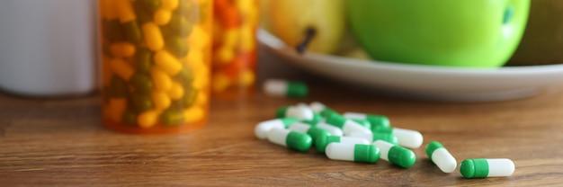 果物やさまざまな錠剤が入ったお皿がテーブルの上にあります。適切な栄養と薬物の害の概念
