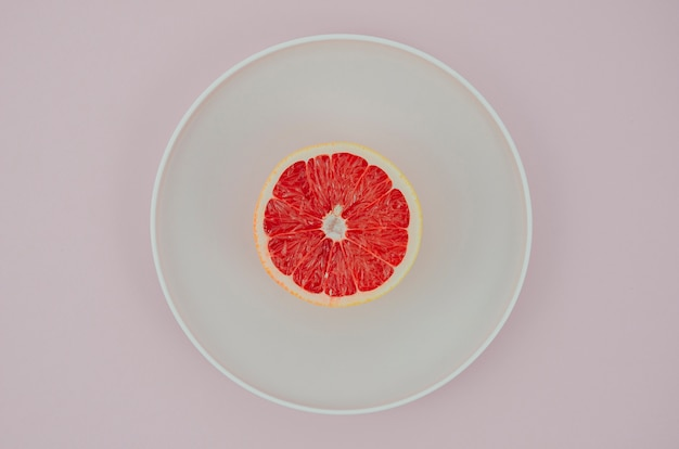 Plate with grapefruit on table